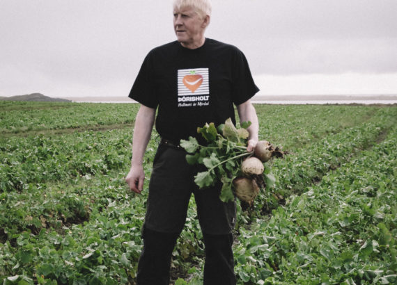 Guðni on a field with turnips in his hands